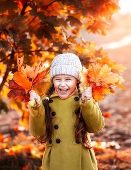 Mała dziewczynka z jesiennym bukietem liści w dłoniach się śmieje