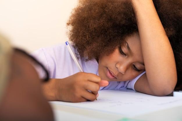 Mała dziewczynka z kędzierzawymi włosami odrabia lekcje