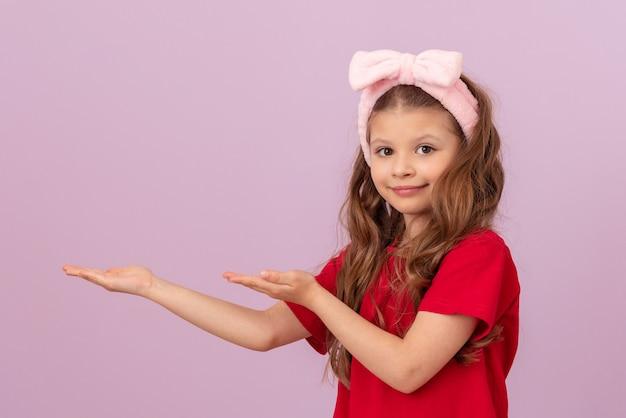 Mała dziewczynka z kokardą na głowie wskazuje dłońmi na reklamę