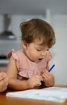 Mała dziewczynka z kolorowymi kredkami podczas malowania w domu