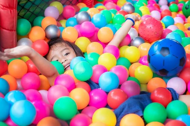 Mała dziewczynka z kolorowymi plastikowymi piłkami. zabawne dziecko zabawy w pomieszczeniu.