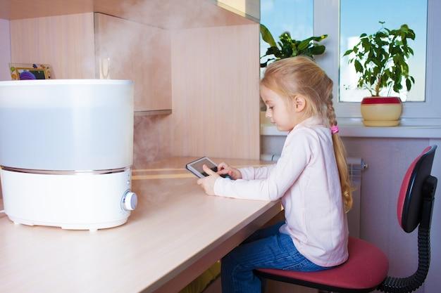 Mała dziewczynka z komputerem typu tablet siedząca przy stole w pobliżu nawilżacza