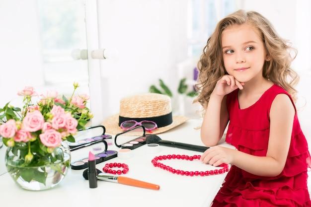 Mała dziewczynka z kosmetykami. jest w sypialni matki, siedzi przy lustrze.