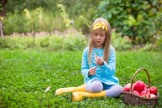 Mała dziewczynka z koszem jabłka w pogodnym jesień dniu