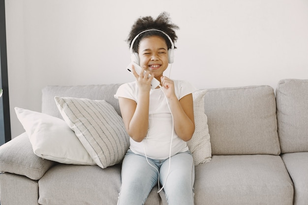 Mała dziewczynka z kręconymi włosami. dziecko suszy muzykę w słuchawkach. baw się dobrze w domu.