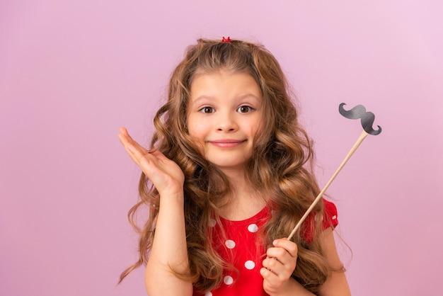 Mała dziewczynka z kręconymi włosami i czerwoną sukienką trzyma fantazyjne wąsy na różowym tle
