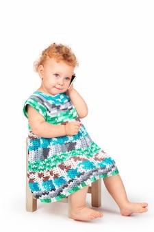 Mała dziewczynka z kręconymi włosami na jasnym tle