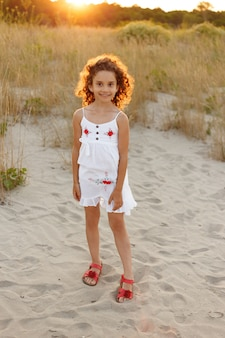 Mała dziewczynka z kręconymi włosami spaceru na plaży