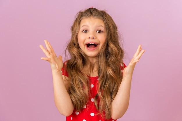 Mała dziewczynka z kręconymi włosami w czerwonej sukience pokazuje swoją radość.