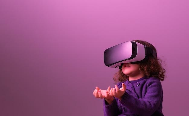 Mała Dziewczynka Z Kręconymi Włosami W Okularach Wirtualnej Rzeczywistości I Fioletowych Ubraniach Trzyma Ręce W Górze, Jakby Coś Podnosiła Premium Zdjęcia