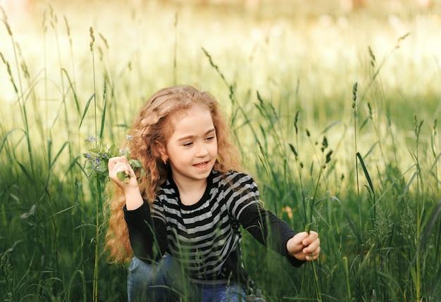Mała dziewczynka z kręconymi włosami zbiera latem kwiaty w parku