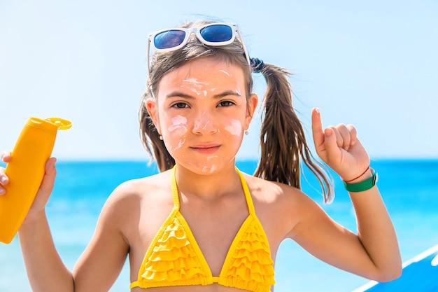 Mała dziewczynka z kremem przeciwsłonecznym na twarzy na plaży
