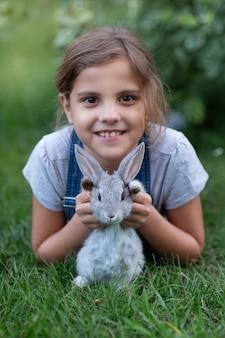 Mała dziewczynka z królikiem w naturze