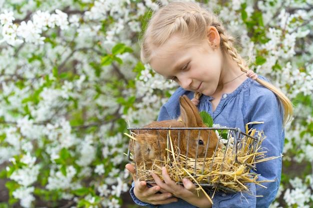 Mała dziewczynka z królikiem w ogrodzie, wiosna