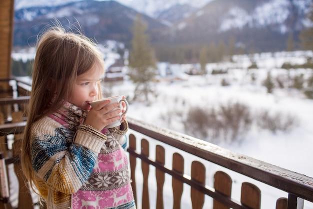 Mała dziewczynka z kubkiem gorącej herbaty