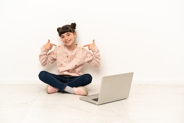Mała dziewczynka z laptopem siedzi na podłodze, dając kciuki do góry gest