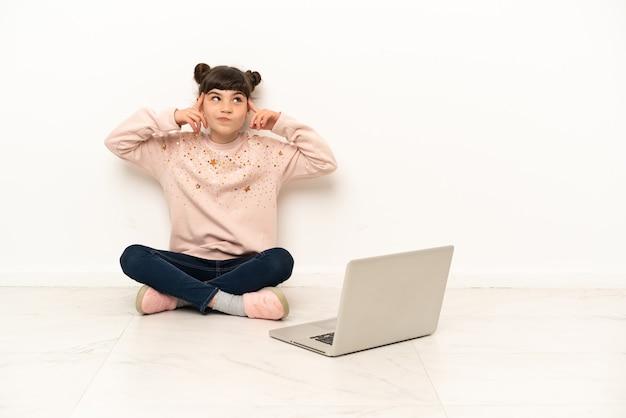 Mała dziewczynka z laptopem siedzi na podłodze, mając wątpliwości i myśli