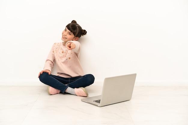 Mała dziewczynka z laptopem siedzi na podłodze, wskazując przód ze szczęśliwym wyrazem twarzy