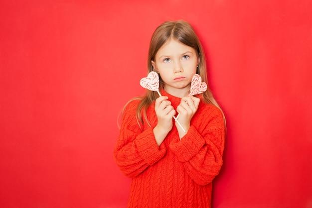Mała dziewczynka z lizakami na czerwonym tle