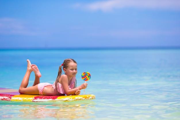 Mała dziewczynka z lizakiem bawić się na desce surfingowej na morzu