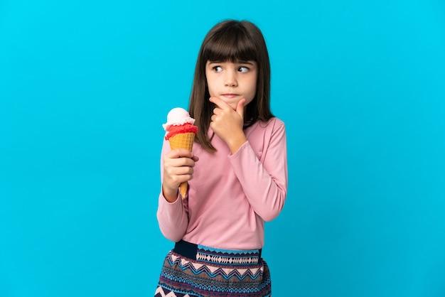 Mała dziewczynka z lodami kornetkowymi na białym tle na niebieskim tle, mając wątpliwości i myślenie