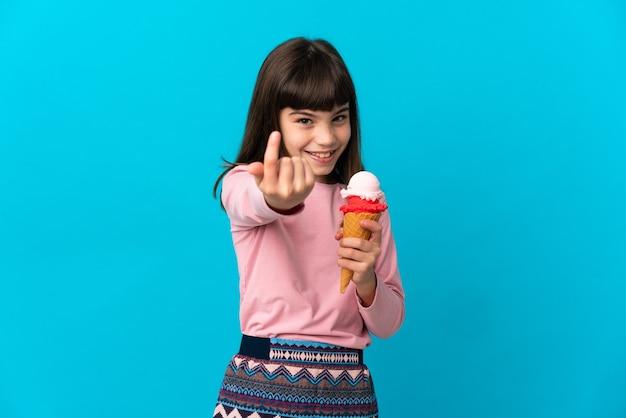 Mała dziewczynka z lodami kornetowymi na białym tle na niebieskim tle robi nadchodzący gest