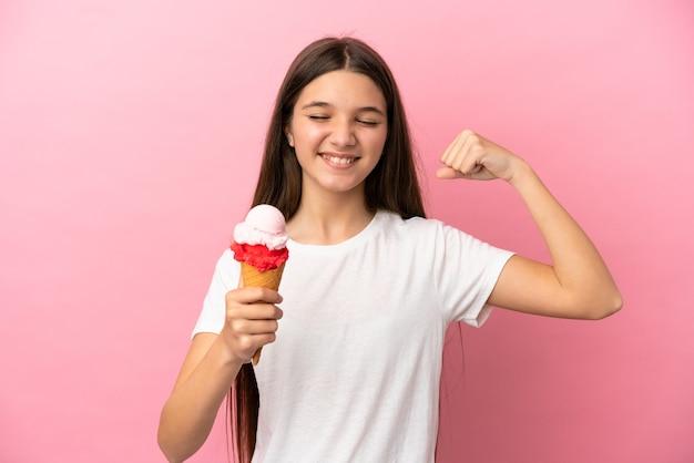 Mała dziewczynka z lodami kornetowymi na izolowanym różowym tle robi silny gest