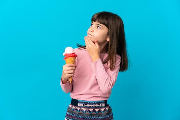 Mała dziewczynka z lody kornet na białym tle
