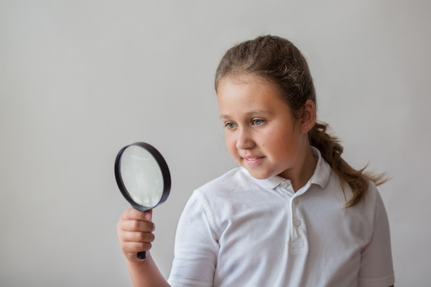 Mała dziewczynka z lupą na szaro
