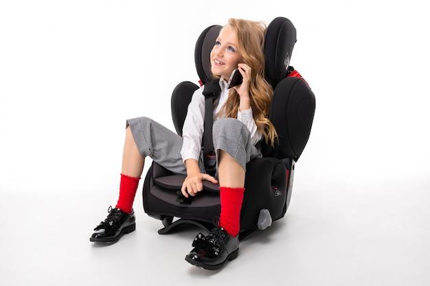 Mała dziewczynka z makijażem i długimi blond włosami, siedząca na krześle samochodowym z telefonem komórkowym i rozmawiająca z przyjaciółmi