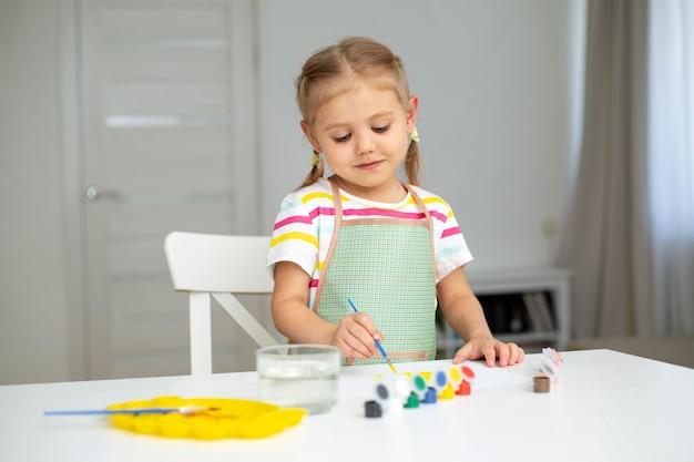 Mała dziewczynka z malowaniem fartucha