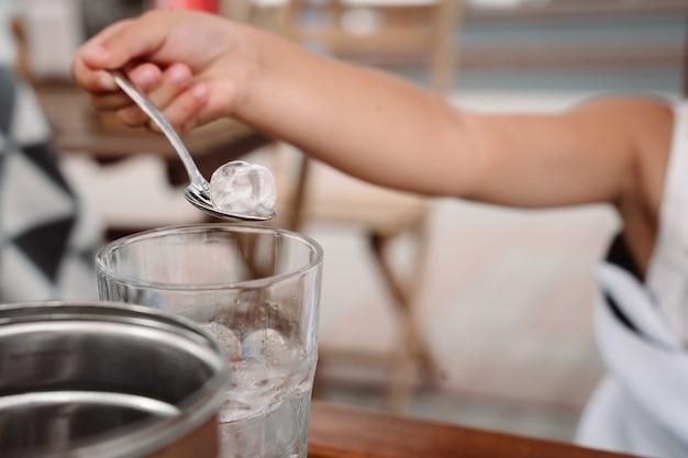 Mała dziewczynka z mamą bawi się kostkami lodu w przytulnej kawiarni. dobre relacje rodziców i dziecka. szczęśliwe chwile razem