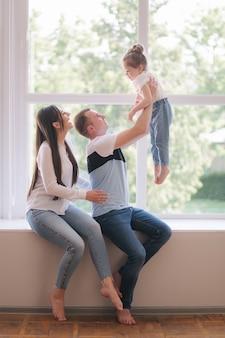 Mała dziewczynka z mamą i tatą siedzi przy oknie