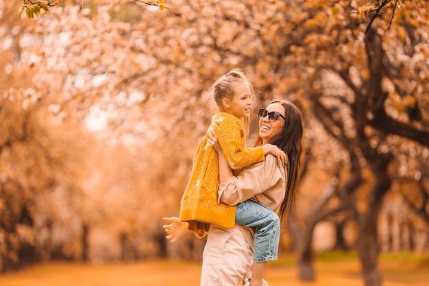 Mała dziewczynka z mamą na świeżym powietrzu w parku w jesienny dzień