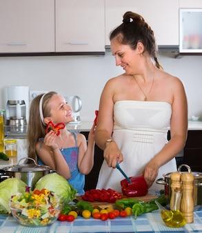 Mała dziewczynka z mamą przy kuchnią