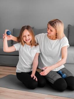Mała dziewczynka z mamą robi sportowi