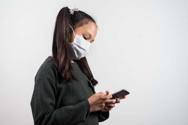 Mała dziewczynka z maską medyczną patrząc na telefon komórkowy na białym tle
