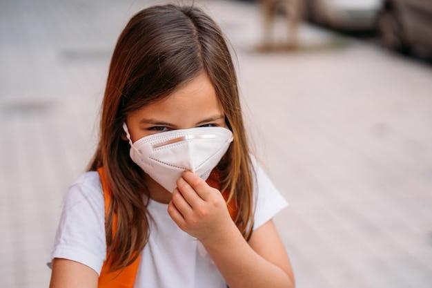 Mała dziewczynka z maską w parku podczas coronavirus pandemii