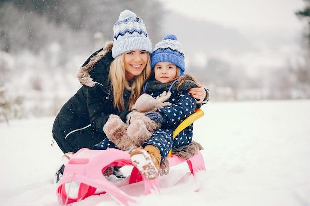 Mała dziewczynka z matką bawić się w zima parku