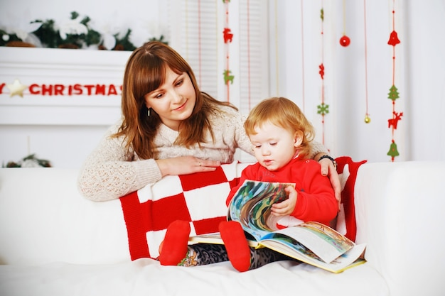 Mała dziewczynka z matką czyta książkę we wnętrzu z dekoracjami noworocznymi.