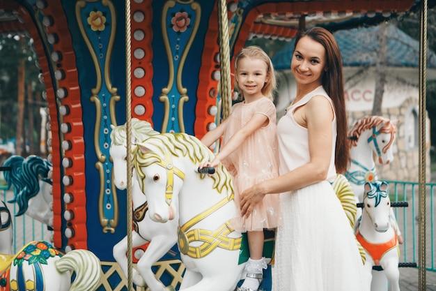 Mała dziewczynka z matką jedzie w parku na zabawkowym koniu na karuzeli. przemysł rozrywkowy, dzień rodzinny, parki dla dzieci, place zabaw