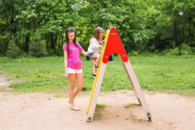 Mała dziewczynka z matką na letnim placu zabaw
