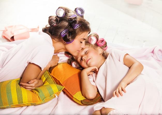 Mała dziewczynka z matką poślizgnie się w łóżku