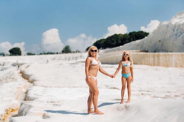 Mała dziewczynka z matką w kostiumach kąpielowych i okularach przeciwsłonecznych na białej górze, rodzina w słoneczny letni dzień na innej planecie, pamukkale, turcja