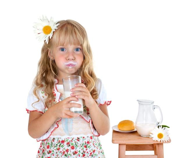 Mała dziewczynka z mlecznymi wąsami po wypiciu mleka na białym tle