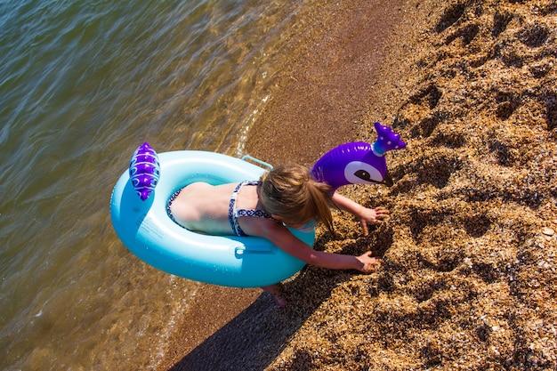 Mała dziewczynka z nadmuchiwanym kółkiem wychodzi z morza na brzeg