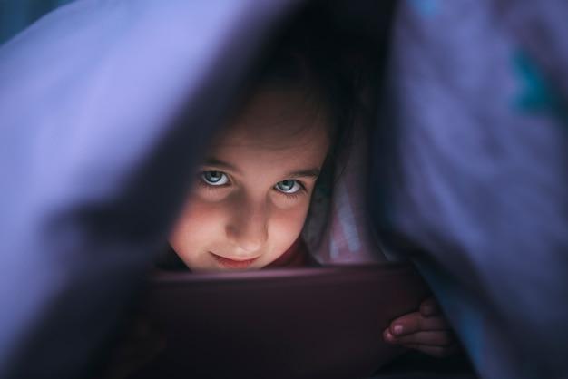 Mała dziewczynka z niebieskimi oczami używać pastylkę pod kołderką