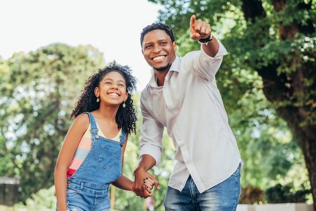 Mała dziewczynka z ojcem, dobrze się razem bawić na spacerze na ulicy
