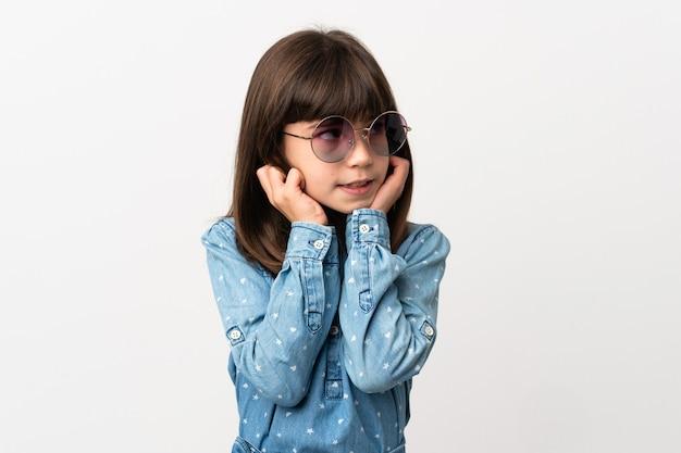 Mała dziewczynka z okularami przeciwsłonecznymi na białym tle sfrustrowana i zakrywająca uszy
