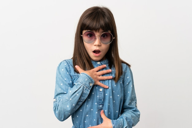 Mała dziewczynka z okularami przeciwsłonecznymi na białym tle zaskoczona i zszokowana, patrząc w prawo
